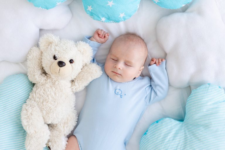 baby-boy-sleeping-bed-lying-his-back-with-soft-teddy-bear-among-pillows (1)