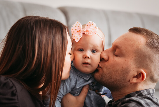 mom-dad-kiss-their-little-daughter-cheek-family-close-up-portrait (1)