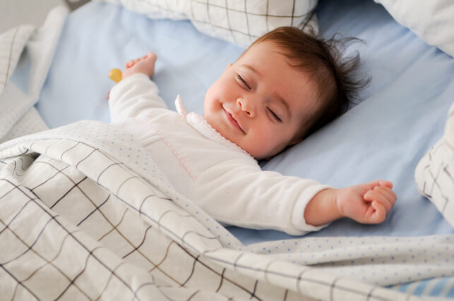 smiling-baby-lying-bed (1)